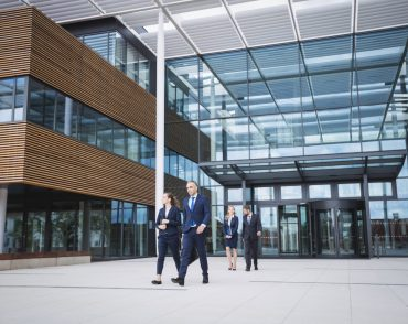 Group of business people walking outside the entrance of an office building
