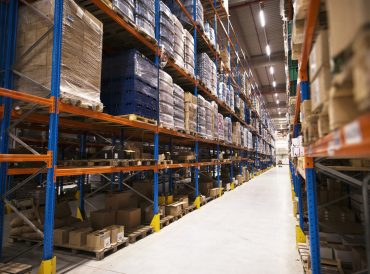 Interior of large distribution warehouse with shelves stacked with palettes and goods ready for the market.