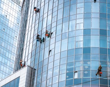 Several workers washing windows in the office building